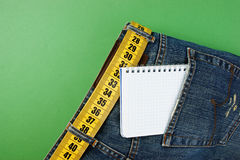 Jeans with meter belt slimming and notebook in pocket. On the green background stock images