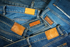 Jeans mit braunem ledernem Aufkleberhintergrund Stockfotografie