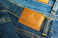 Jeans mit brauner lederner Aufklebernahaufnahme Lizenzfreies Stockfoto