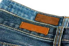 Jeans mit dem ledernen Aufkleber lokalisiert auf Weiß Lizenzfreie Stockfotografie