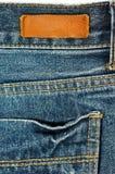 Jeans mit ledernem Aufkleber und Tasche Stockfotos