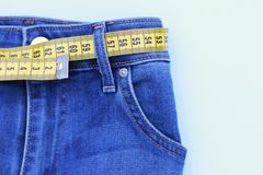 Jeans och mätaämne för viktförlust på blå bakgrund arkivfoton