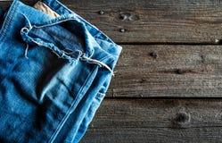 Jeans ordinatamente piegati su fondo di legno Abbigliamento, modo, stile, stile di vita Immagine Stock Libera da Diritti