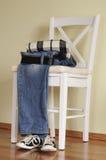 Jeans, overhemd, tennisschoenen en een witte stoel Royalty-vrije Stock Afbeelding