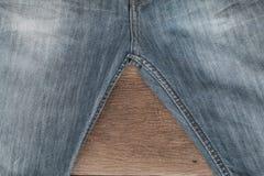 Jeans på en brun träbakgrund Arkivfoto