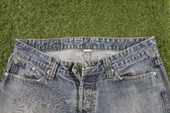 Jeans på en konstgjord gräsbakgrund Arkivfoto