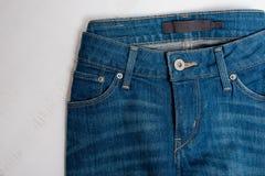 Jeans på vit träbakgrund för begreppsframsida för skönhet blå ljus kvinna för makeup för mode close upp royaltyfria foton