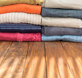 Jeans Pants and Classic Wool Sweaters on Wood. Many Colorful Clothing Neatly Stacked in Two Rows on Natural Wooden Board Desk Illuminated by Sunlight Stripes Royalty Free Stock Image