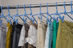 Jeans pants hung on hangers in a row Royalty Free Stock Photos