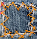 Jeans patch. Patch in blue jeans material with orange stitches makes a square frame Royalty Free Stock Images