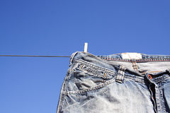 Jeans pegged to the wash line. A pair of denim jeans pegged to a wash line. The clear brilliant blue sky behind creates a perfect background Stock Photos