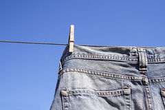 Jeans pegged to the wash line. A pair of denim jeans pegged to a wash line. The clear brilliant blue sky behind creates a perfect background Stock Photo