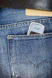 Jeans & phone. The mobile phone sticks out of a back pocket jeans royalty free stock images