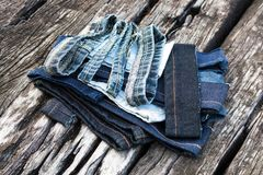 Jeans pieces on old wood. Close-up of fragments of jeans left over from repair, sewing, stacked on old decayed wood stock photo