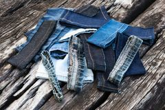 Jeans pieces on old wood. Close-up of fragments of jeans left over from repair, sewing, stacked on old decayed wood royalty free stock photo