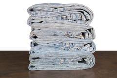 Jeans piegati sul pavimento di legno Immagini Stock