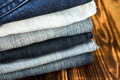 Jeans pile on wooden board Stock Photo