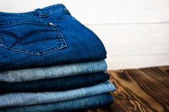 Jeans pile on wooden board Royalty Free Stock Image