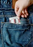 Jeans pocket with condom in hand Stock Photography