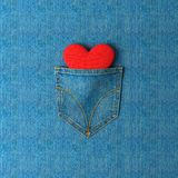 Jeans pocket with a heart inside on a jeans background. 3d illus. Decorative background. Jeans pocket with a heart inside on a jeans background. Pocket with a Stock Images