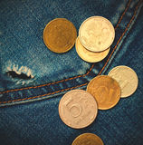 Jeans pocket with hole and coins Stock Photos