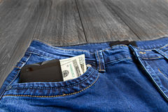 Jeans pocket with money and phone Royalty Free Stock Photos