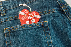 Jeans with red Christmas heart in pocket. Stock Photography