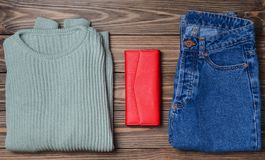 Jeans, a red purse, a mint-colored sweater on a wooden surface. Women& x27;s clothing and accessories. Top view. Flat lay Stock Images