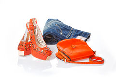 Jeans, red sandals and red leather handbag. Isolated Royalty Free Stock Photography