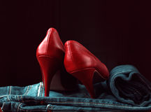 Jeans and red shoes. Over black Royalty Free Stock Images