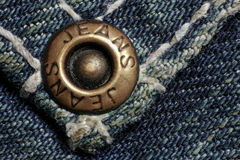 Jeans rivet, old dirty jeans, macro photo. Fashion jeans button. Sign JEANS JEANS on bronze part of button. Blue denim Stock Images