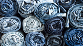 Jeans. Roll blue denim jeans arranged in stack Royalty Free Stock Photography