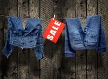 Jeans, sale inscription on clothesline Stock Photo