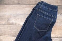 Jeans scuri disposti su un pavimento di legno Immagine Stock