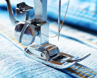 Sewing machine and blue jeans fabric Stock Photos