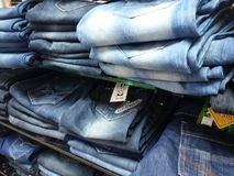 Jeans of various shades of blue on display at shop shelves. Various denim jeans folded and messily stacked on display at a shop Stock Photos