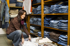 Jeans shop woman. A pretty brunette woman, saleslady, arranging clothes on shelves in a jeans shop Royalty Free Stock Photography