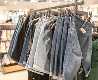 Jeans shorts on the store shelf. Fashionable clothes on the shelves in the store. Jeans hanging on the vests in the fashion store. Showcase, sale, shopping royalty free stock images