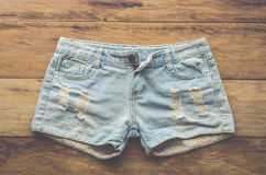 Jeans shorts on the wooden floor Royalty Free Stock Photo