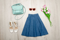 Jeans skirt, glasses, white shoes, handbag and a bouquet of tulips. Fashionable concept. Wooden background Stock Photos