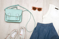 Jeans skirt, glasses, white shoes, white top and handbag. Fashionable concept. Wooden background Royalty Free Stock Photos