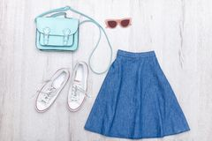 Jeans skirt, glasses, white sneakers and handbag. Fashionable concept. Wooden background Royalty Free Stock Images