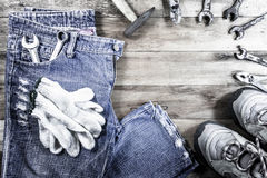 Jeans and sneakers with gloves and tools on a wood background Royalty Free Stock Images