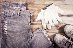 Jeans and sneakers with gloves on a wood background Stock Image