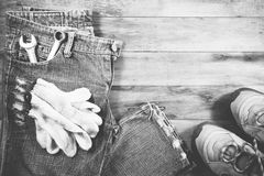 Jeans and sneakers with gloves on a wood background. Stock Photography