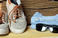 Jeans sneakers and sunglasses Stock Photos