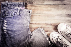 Jeans and sneakers on a wood background Stock Image