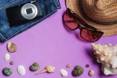 Jeans solglasögon, fotokamera, brun hatt, snäckskal på lila bakgrund Loppbegrepp för bästa sikt med Copyspace Arkivbild