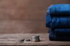 Jeans stacked with coins on a wooden background. Jeans stacked on a wooden background stock photography