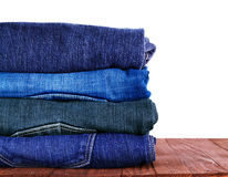 Jeans stacked on a wooden background. Jeans stacked on, a wooden background Stock Photo